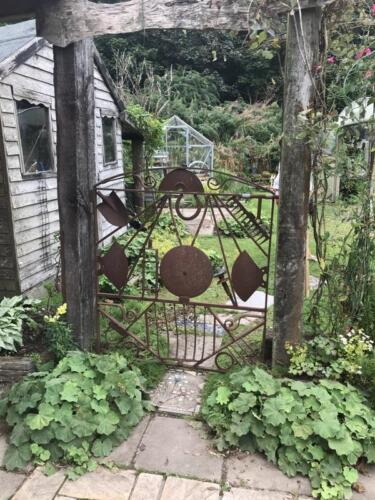 Gate fashioned from old garden tools.
